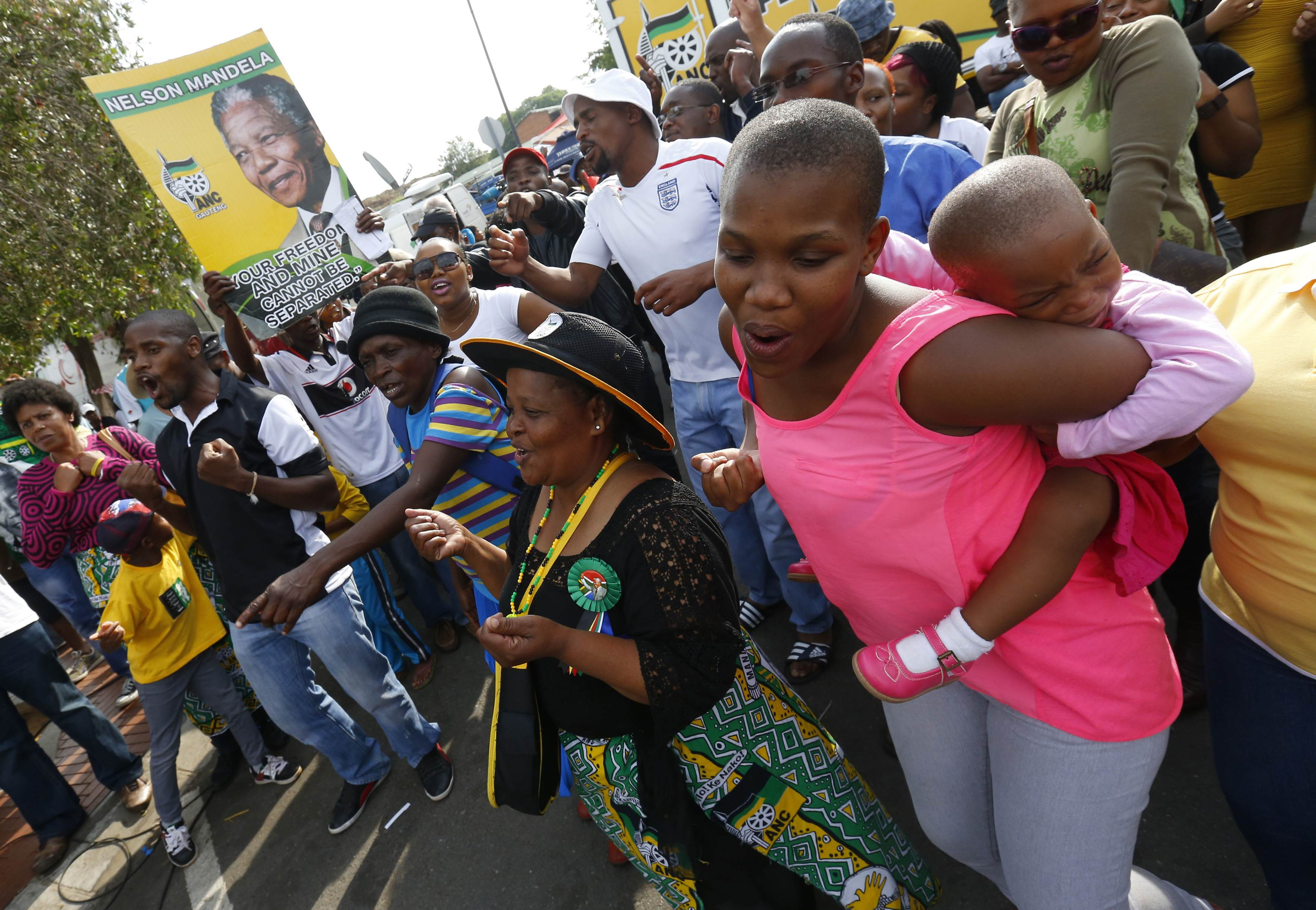People dance during a gathering of mourners on Vilakazi Street in Soweto where the former South African President Nelson Mandela resided when he lived in the township
