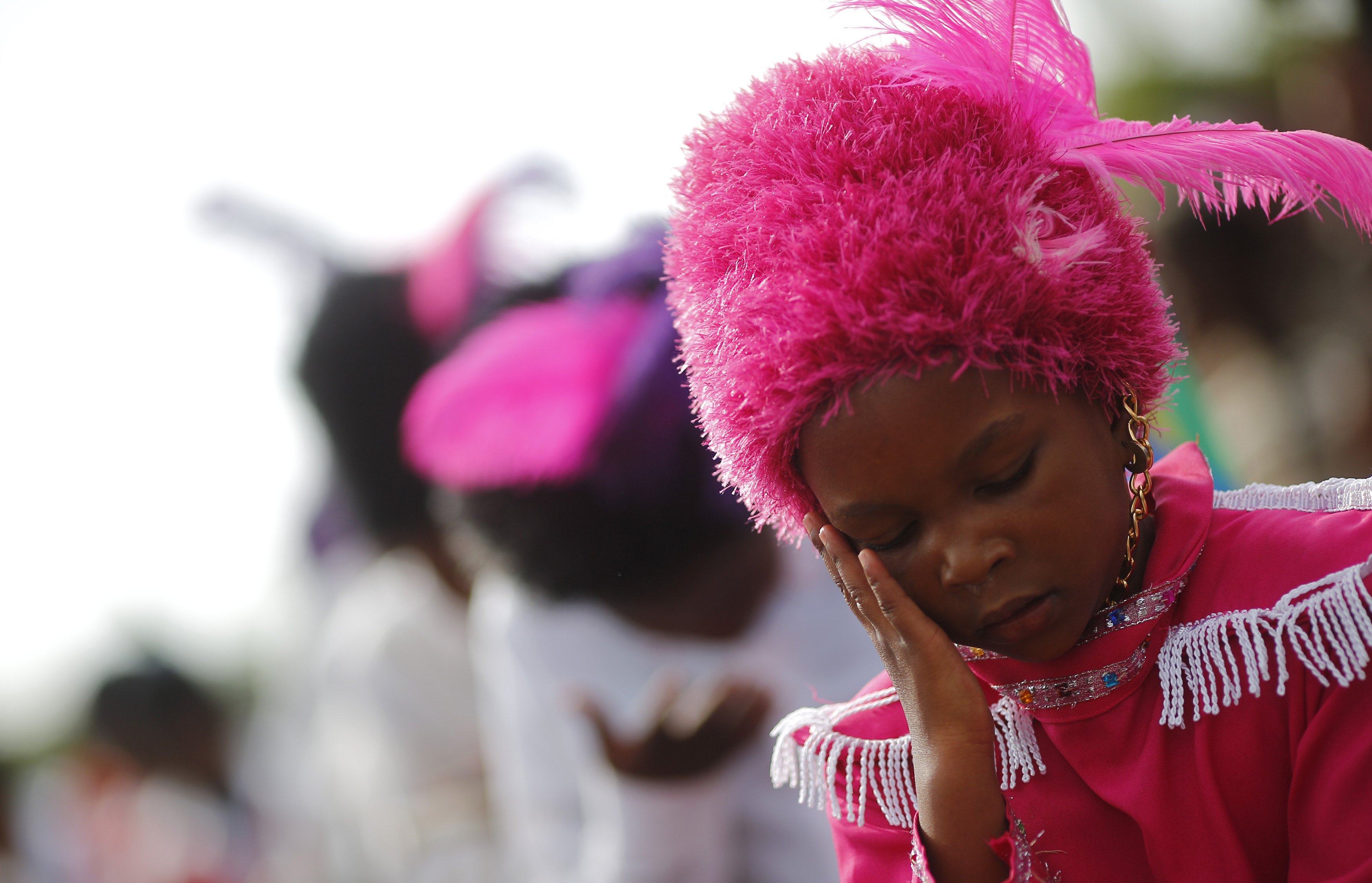 A young girl wipes her face as she performs in a group of dancers outside Mandela house in Soweto