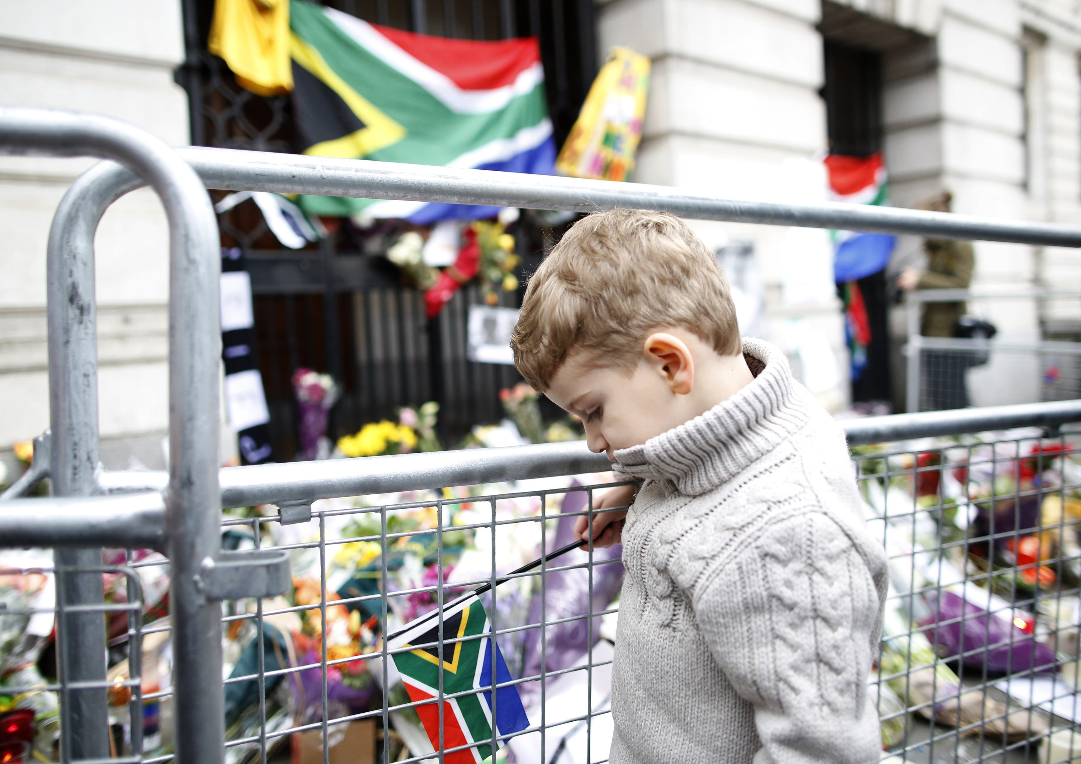 South African boy, Grant, looks at flowers laid in memory of Nelson Mandela outside the South African High Commission in central London