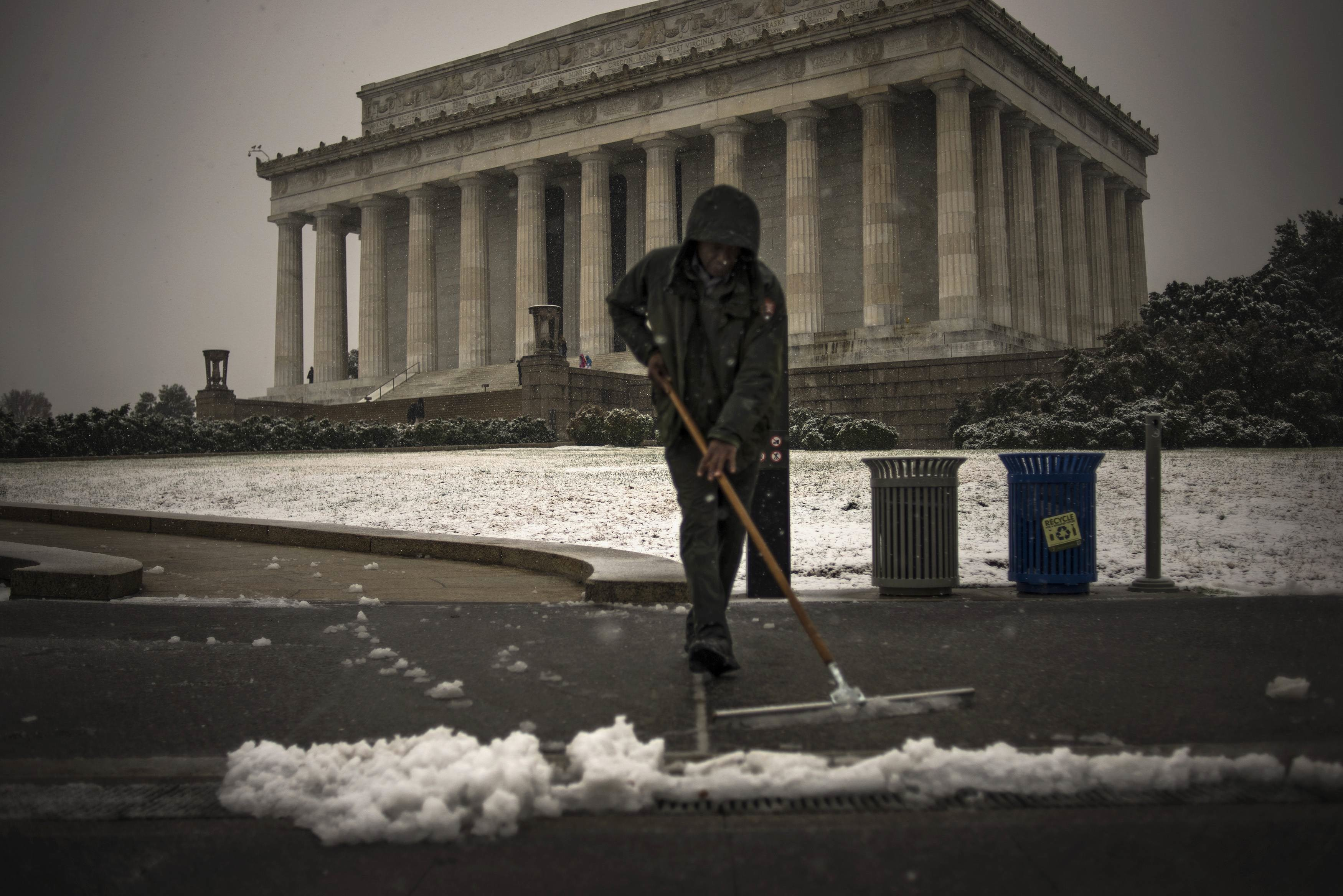 A National Park Service employee clears snow and slush from a walkway to the Lincoln Memorial in Washington