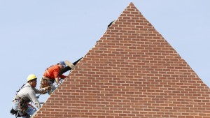 Builders work on the roof of a new housing construction site in Alexandria