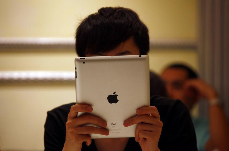 A man looks at his iPad while sitting in a cafe in central Beijing