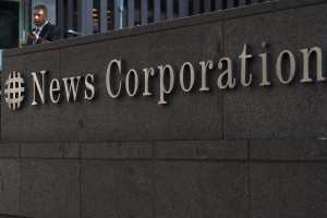File photo of a passer-by standing in front of the News Corporation building in New York