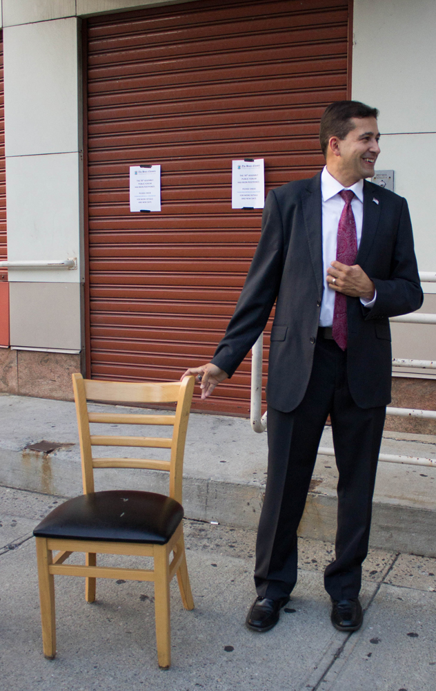 Fernando Tirado and an empty chair meant for Assemblyman Jose Rivera