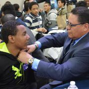 Mentor Eliezer Rodriguez pins one of his 'Aim High' mentees.