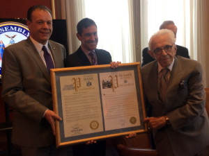 Assemblyman Gjonaj and Senator Klein present Norman Gershman with a framed proclamation.