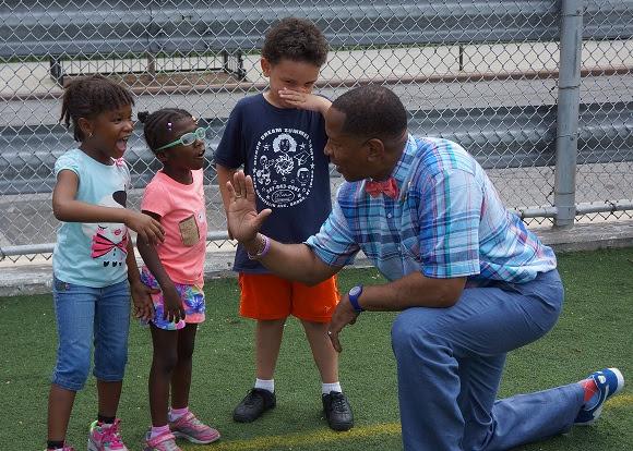 New York City Councilmember Andy King helps children warm up for activities.