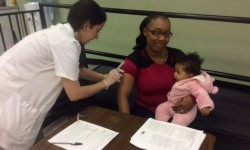 Ms. Tameka Santiago with her eight month old daughter receiving flu vaccination from Maria Troia, PharmD Pharmacy Manager, Walgreens