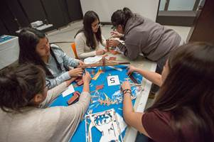 Five students construct a model of the Brooklyn Bridge at the DDC STEAM education initiative's annual 'Introduce a Girl to Architecture, Engineering and Construction' event on Pi day.