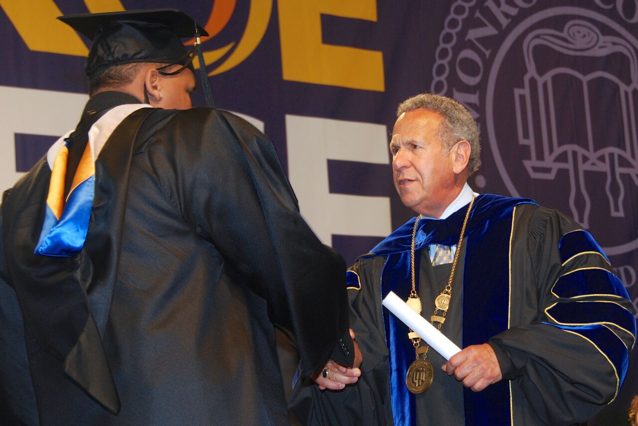 Monroe College Graduation -- President Stephen Jerome confers a degree to a graduating student.