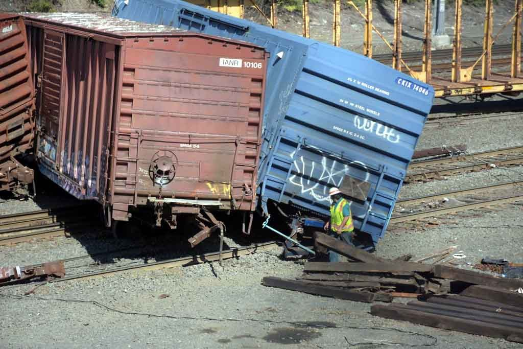 Train crews spend the day removing the damaged train and repairing torn-up track.--Photo by Edwin Soto