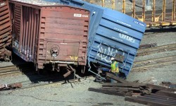 Train crews spend the day removing the damaged train and repairing torn-up track.  Photo by Edwin Soto.