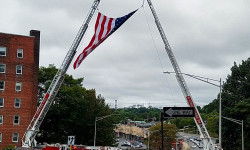 Firefighters hoist an American flag as the funeral procession for Battalion Chief Michael Fahy heads from the Annunciation Church in Yonkers to the Gate of Heaven Cemetery in Hawthorne, NY.--Photo by Andre Rivera