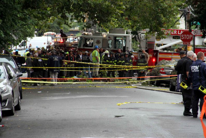 A sea of firefighters stand around debris that landed on the street and a parked vehicle after an explosion on West 234 Street. -- Photo by David Greene