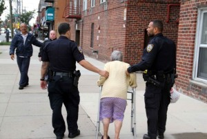 The unidentified officers escort the woman to the entrance of her building. Photo by David Greene.