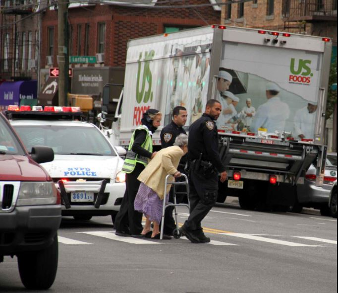 A crossing guard and two police officers assist an elderly woman crossing the street in Morris Park. Photo by David Greene