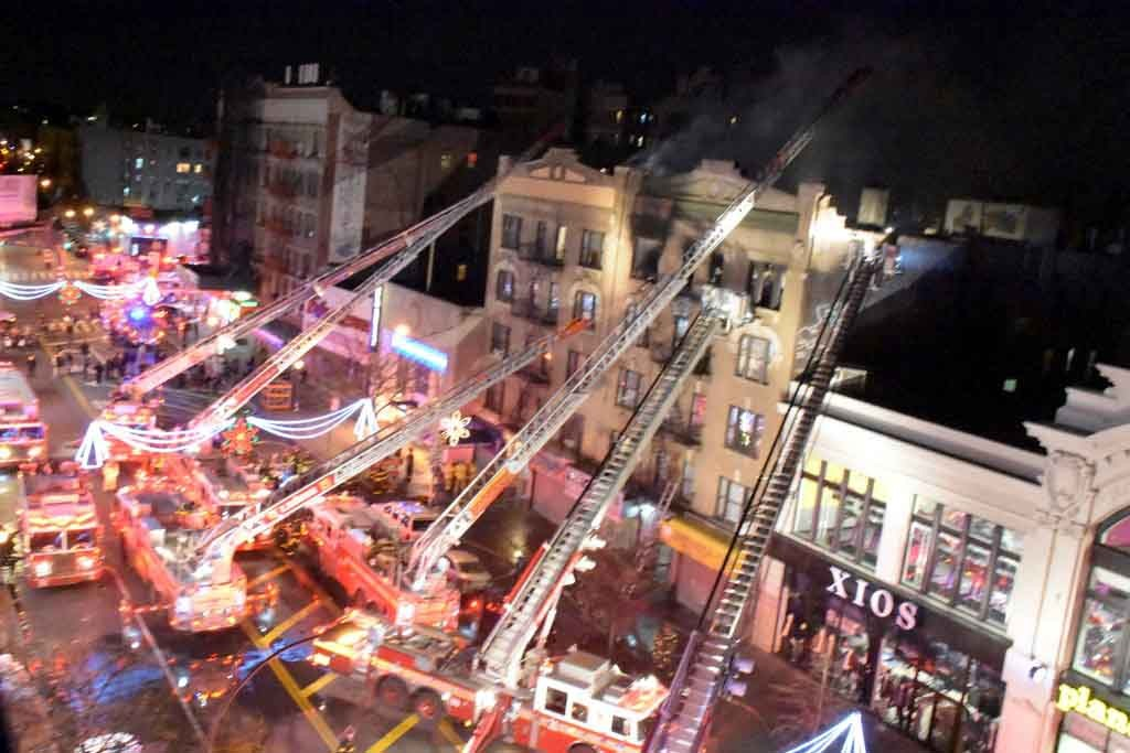The FDNY used 6 tower ladders to battle a fire on the top floor of a 5-story building.--Photo by Edwin Soto