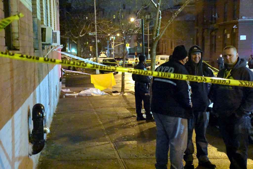 Police guard the crime scene after Jose Morales, 41, was shot dead at the corner of East 175 Street and Weeks Avenue on Sunday, December 11. -- Photo by Edwin Soto