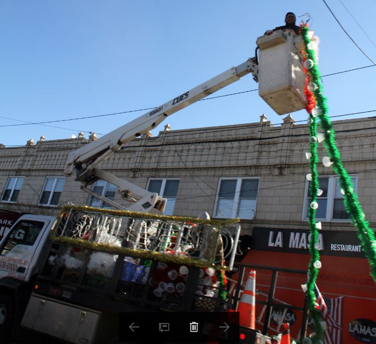 Workers are busy installing holiday lights along Morris Park Avenue. Photo by David Greene