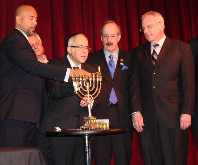 December 22, 2016: Borough President Ruben Diaz Jr. (far L) is assisted by Rabbi Israel Greenberg (middle L), U.S. Congressman Eliot Engel, & NYS Assemblymember Jeffrey Dinowitz in lighting the menorah