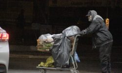 The used-clothing thief wheels away a shopping cart full of items that was headed to area churches and organizations. --Photo by David Greene