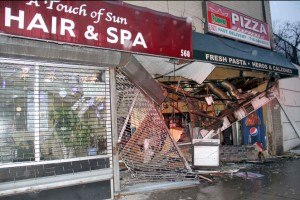 The owner of Famous Pizza Express says it will be several months before he can re-open after an SUV plowed through the storefront on Monday. Photo by David Greene
