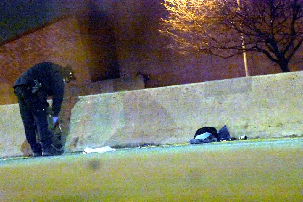 A police officer examines a man's personal belongings after being struck and critically injured on the Bruckner Expressway Sunday night.--Photo by Edwin Soto