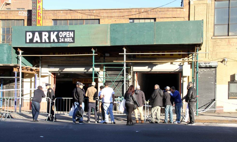 A dozen people wait for word late Sunday outside of Dr. Parking on Jerome Avenue.--Photo by David Greene