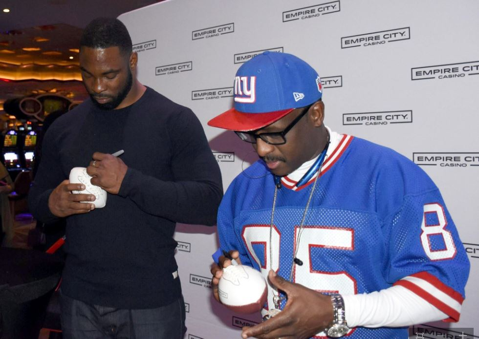 Former NY Giants (l-r): Justin Tuck and Stephen Baker sign autographs for fans during a Super Bowl viewing party at Empire City Casino on Yonkers, N.Y. Photo courtesy of Empire City Casino