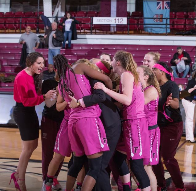 Fordham Lady Rams Coach Gaitley celebrates record win with players. Phot credit: Robert Cole.