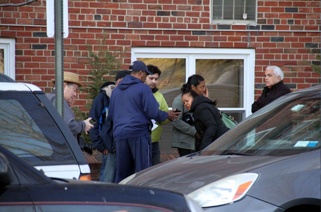 Neighbors console one another after an off-duty NYPD sergeant was found dead inside his apartment. Photo by David Greene