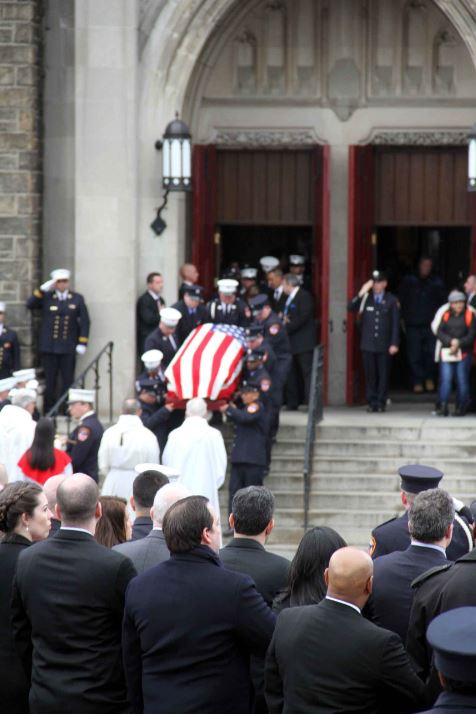 The flag-draped coffin containing the body of EMT Yadira Arroyo is carried out of the St. Nicholas of Tolentine Roman Catholic Church of University Avenue. Photo by David Greene