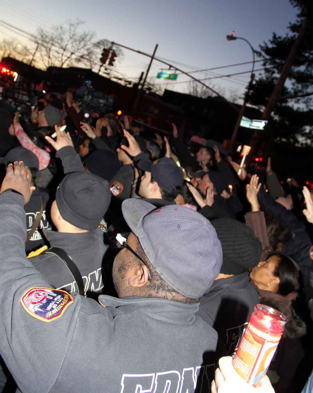 Firefighter's and paramedics hold candles for fallen EMT Yadaira Arroyo, a 14 year member of the FDNY.--Photo by David Greene