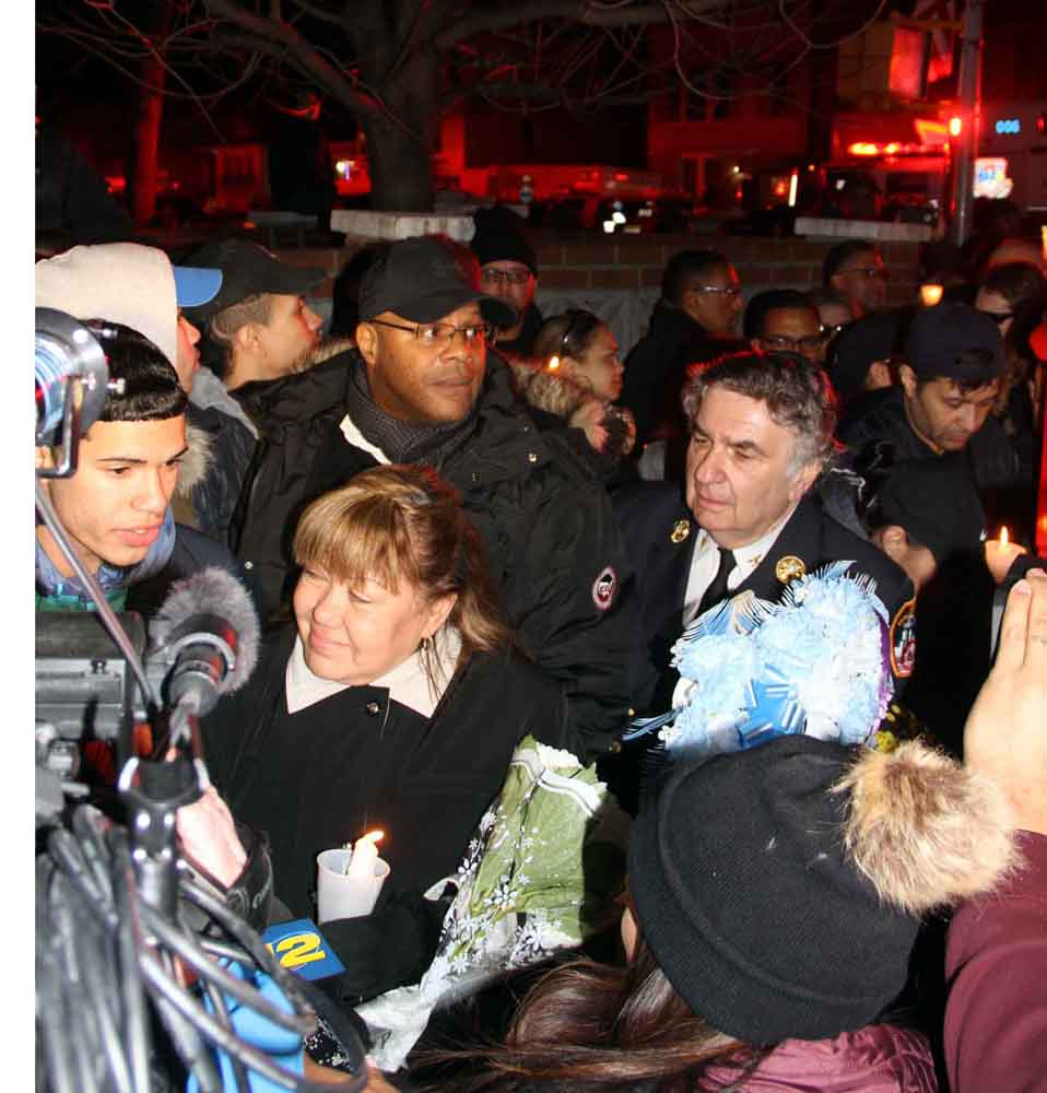 Members of the Arroyo family join with their FDNY family and the Soundview community at the emergency call box on White Plains Road and Watson Avenue where she was critically injured.--Photo by David Greene