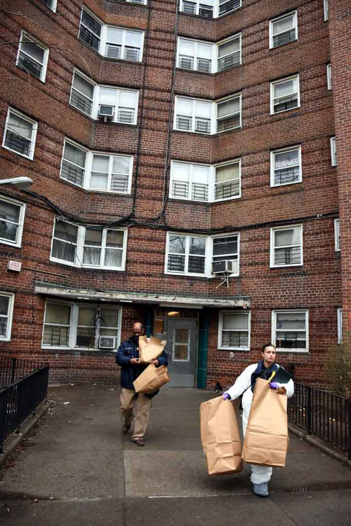 Members of the NYPD's Crime Scene Unit remove evidence after a young woman was shot to death inside Forest Houses. Photo by Edwin Soto