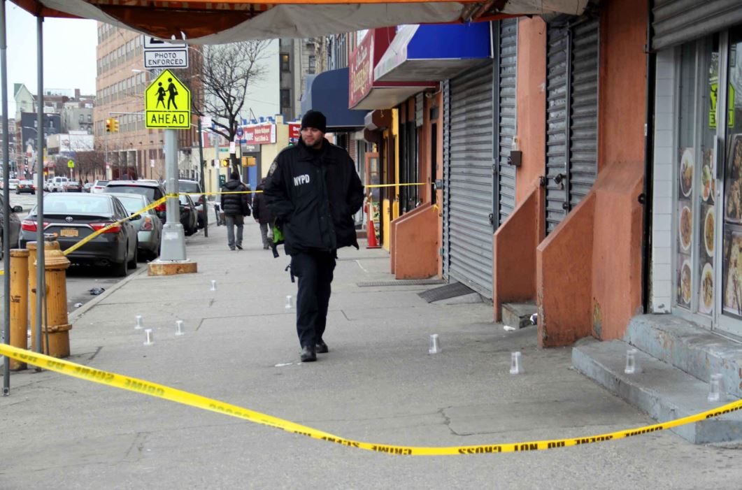 A police officer guards the 9 shell casings found at the scene of an early morning shooting in Bedford Park. Photo by David Greene