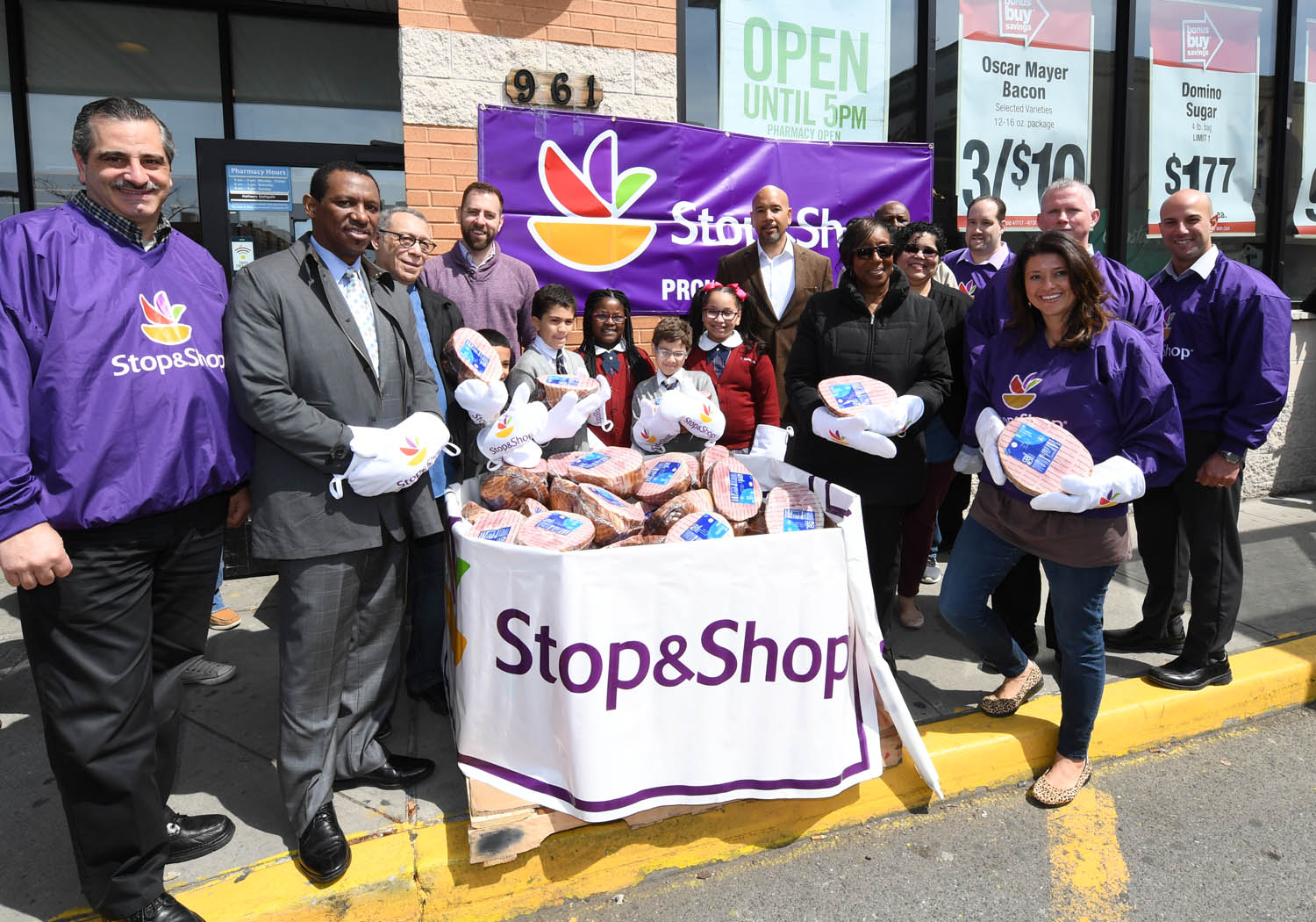 BX Hams-Group Stop & Shop executives at the E. 174th supermarket in the Bronx joined by (l.-r.) Rev. Malobe Sampson of Thessalonia Church; Bishop Angelo Rosario of the Bronx Clergy Task Force; Christopher Bean of POTS (Part of the Solution); students from the neighboring St. Thomas Aquinas School; Bronx Borough President Ruben Diaz Jr.; Mary Brown of Thessalonia Church; and Rev. Lourdes Pena of New Season Christian Center, at a bin full of Easter hams the group helped unload as part of the supermarket's donation of 1,000 hams to five community organizations on April 13. (Credit: Stop & Shop)