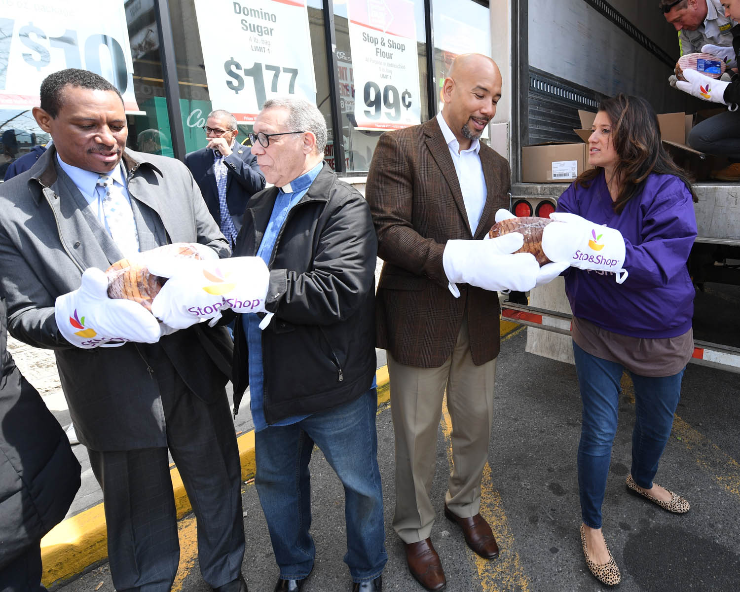 BX Hams-Unload 1 (L.-R.) Rev. Malobe Sampson of Thessalonia Church; Bishop Angelo Rosario of the Bronx Clergy Task Force; Bronx Borough President Ruben Diaz Jr.; and Cindy Carrasquilla of Stop & Shop Metro NY pass Easter hams hand-to-hand in the parking lot of the E. 174th supermarket in the Bronx on April 13. The supermarket donated 1,000 Easter hams to five social service agencies that provide assistance to Bronxites in need. (Credit: Stop & Shop)