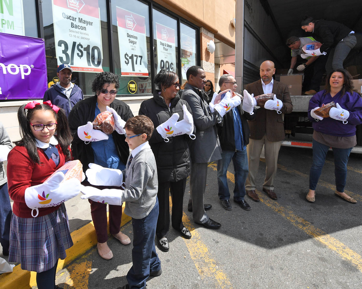 BX Hams-Unload 2 Bronx Borough President Ruben Diaz Jr. (2nd from r.) and Cindy Carrasquilla of Stop & Shop NY Metro (far r.) were joined by representatives from local social service agencies and St. Thomas Aquinas School students to help unload hams in the parking lot of the E. 174th supermarket in the Bronx on April 13. The supermarket donated 1,000 Easter hams to five social service agencies that provide assistance to Bronxites in need. (Credit: Stop & Shop)