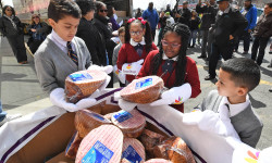 BX Hams-Unload 3 Students from St. Thomas Aquinas School deposit hams into an awaiting bin to help unload a portion of the 1,000 Easter hams Stop & Shop donated to five local social service agencies during an event celebrating the donation at the E. 174th supermarket in the Bronx on April 13. During the event Bronx Borough President Ruben Diaz Jr., Stop & Shop executives and representatives with each of the recipient agencies helped unload hams hand-to-hand from an 18-wheeler truck. (Credit: Stop & Shop)