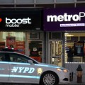 Police investigate the latest grand larceny of a cell phone store on Morris Park Avenue.--Photo by David Greene