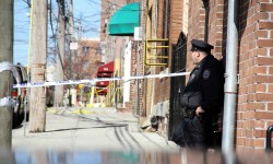 A police officer guards the scene where Margarita Franco, 26, was found shot to death along East 214 Street in Williamsbridge. Photo by David Greene
