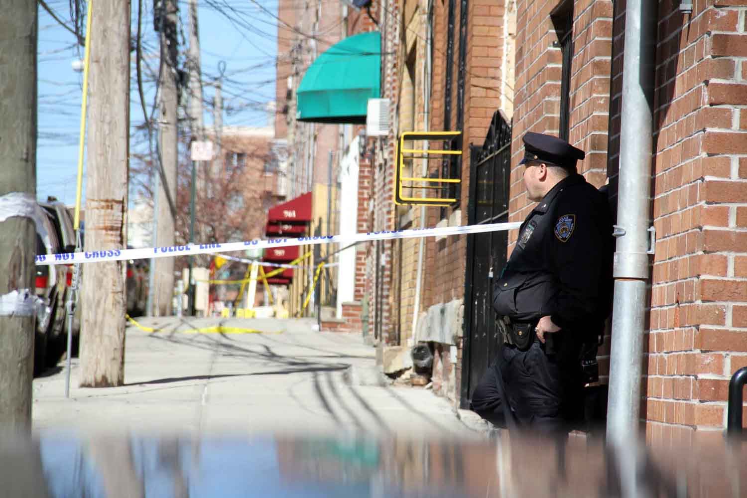 A police officer guards the scene where Margarita Franco, 26, was found shot to death along East 214 Street in Williamsbridge.--Photo by David Greene