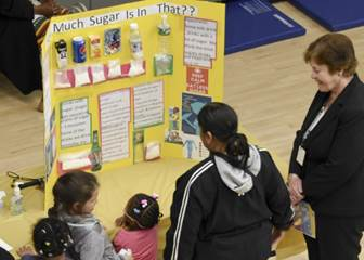 "Sugar New York Institute for Special Education Executive Director Bernadette Kappen (far right) and students learn about sugar consumption from one of the ""Healthy Nutrition"" themed experiments on display at the school's 15th annual science fair on April 5. More than 200 pre-school to high school students with visual impairments, emotional challenges and developmental delays participated in the event. (Credit: James Rivera)"