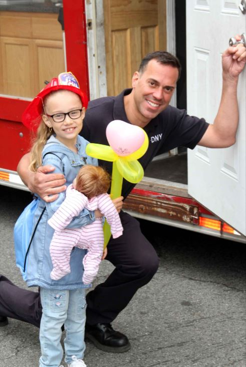 A young girl poises for a photo with a fireman during the teddy bear hospital event at Montefiore Hospital's Wakefield Campus. Photo by David Greene