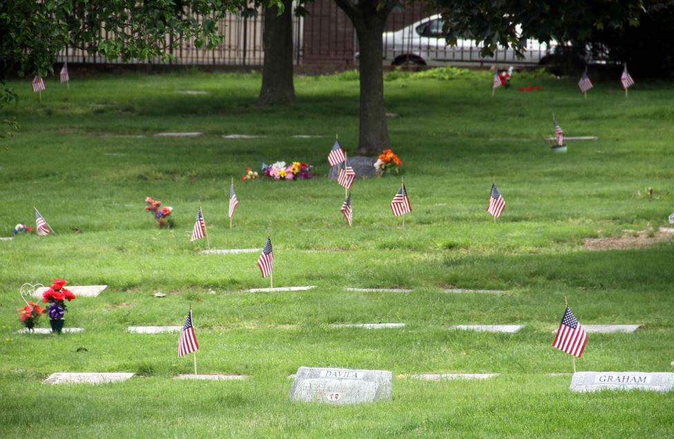 Flags mark the graves of the Zinnia section of Woodlawn Cemetery where many veterans of the Korean War are laid to rest. Photo by David Greene