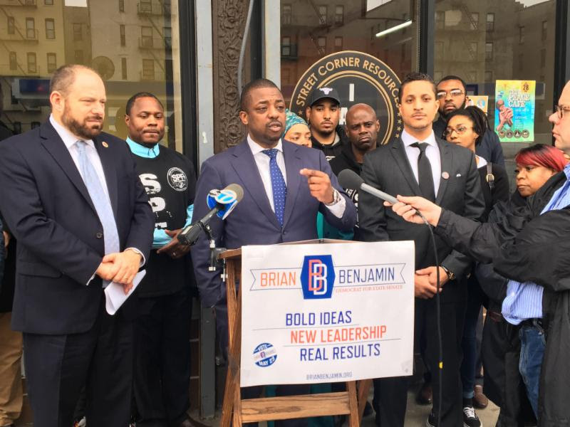 Brian Benjamin (at podium), candidate for State Senate, joins NYC Council Member Rory Lancman (left) to unveil a new three-point strategy for closing Rikers Island in three years as Akeem Browder (right) and advocates look on