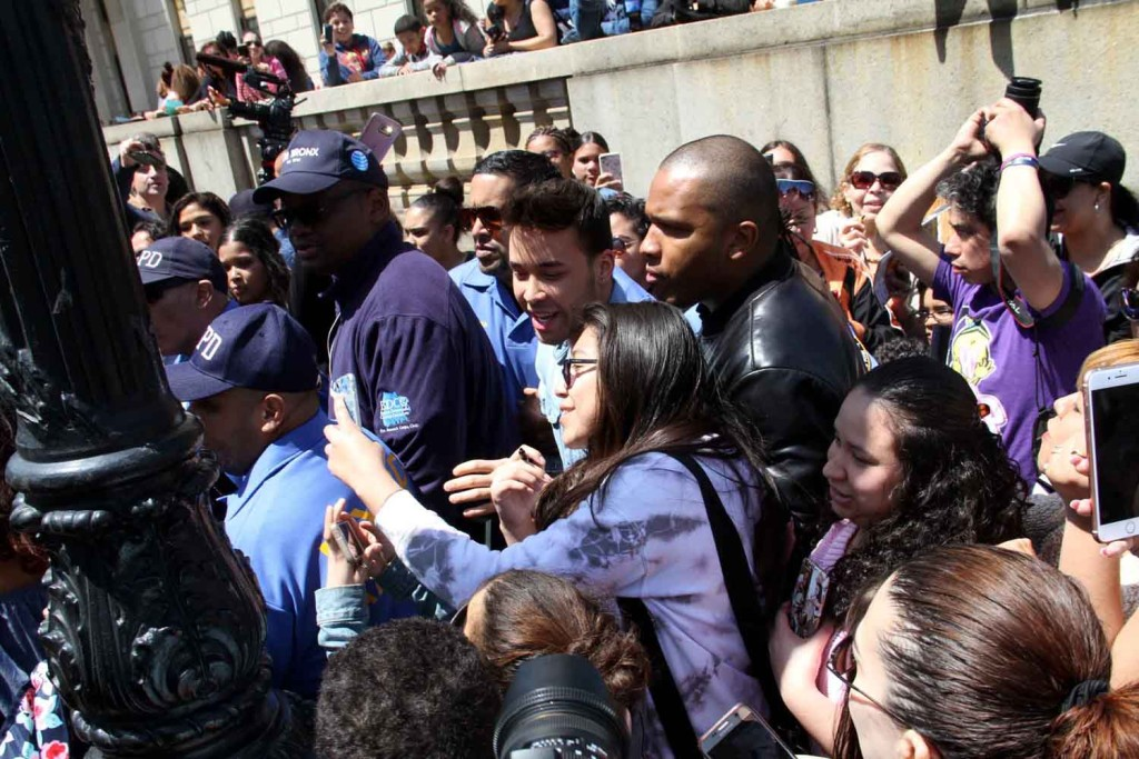 Under heavy police protection, Latin music star Prince Royce poises for a photo with a fan outside the Bronx County Courthouse.--Photo by David Greene