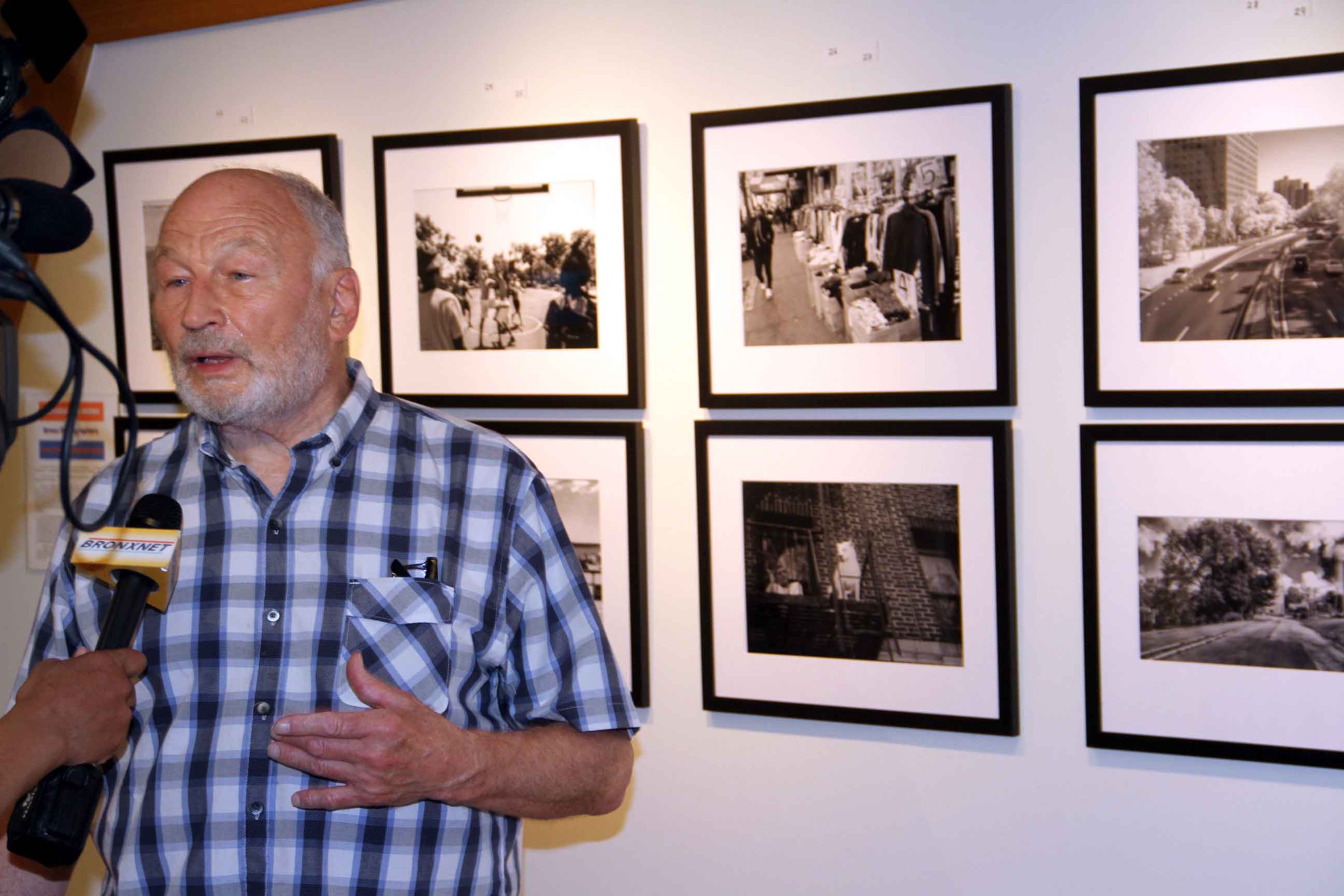 Photographer and organizer Walter Pofeldt is interviewed next to some of his work. Photo by David Greene
