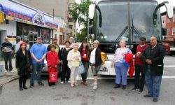 Members of Community Board # 7 gather in front of rented tour bus that took members for a tour through the community. Photo by David Greene